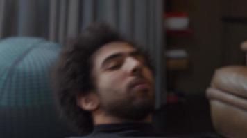 jovem homem do Oriente Médio deitado no chão da sala de estar fazendo abdominais