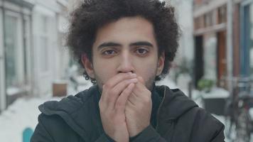 close-up de homem do Oriente Médio, olhando para a lente da câmera, soprando ar quente nas mãos, esfregando video