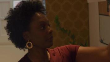 mulher negra madura desce as escadas do corredor, pega o casaco, veste, olha no espelho, tira a máscara facial, coloca, ajusta video