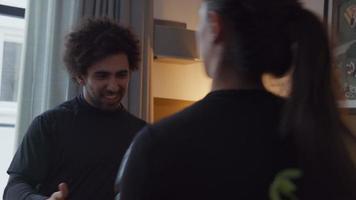 jovem homem do Oriente Médio em pé na sala de estar com as mãos na frente, pegando socos em uma jovem mestiça com luvas de boxe