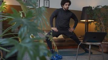 junger Mann aus dem Nahen Osten im Wohnzimmer, stehend, Laptop vor sich betrachtend, streckt Bein, beugt anderes Bein, Hände auf Oberschenkeln