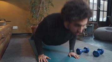 jovem homem do Oriente Médio na sala de estar fazendo flexões no tapete de ioga, parecendo sério