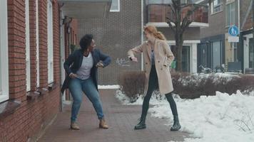 zwarte rijpe vrouw en jonge blanke vrouw staan buiten, lachend, tegenover elkaar op afstand, ellebogen aanraken, als hallo video