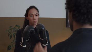 jovem mestiça com luvas de boxe pratica boxe com jovem homem do Oriente Médio, de mãos dadas na frente dele, mulher falando