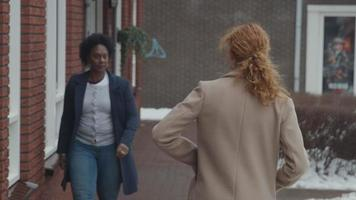 zwarte rijpe vrouw loopt naar buiten en ontmoet jonge blanke vrouw, die van de andere kant komt en met ellebogen gedag zegt video