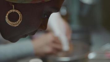 svart mogen kvinna pratar, svart man bär glasögon, lägger tårtblandning i skål, kvinnans hand sätter flaska mjölk bredvid skålen