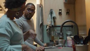 svart mogen kvinna och svart man bär glasögon som står vid köksbänken, läser recept, man får en flaska mjölk, sätter den på bänken