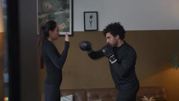 jovem homem do Oriente Médio com luvas de boxe, socos de várias maneiras nas mãos de uma mulher mestiça, as mãos postas à sua frente