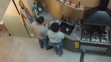 svart mogen kvinna och svart man bär glasögon, står vid köksbänken bredvid henne, mannen håller flaskan, kvinnan tar flaskan från hyllan framför henne