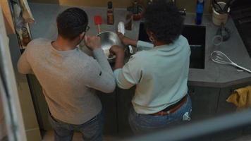 svart mogen kvinna och svart man bär glasögon, står vid köksbänken bredvid henne, kvinna rör om med sked i skål, man häller olja i locket på flaskan, lägger olja i skålen