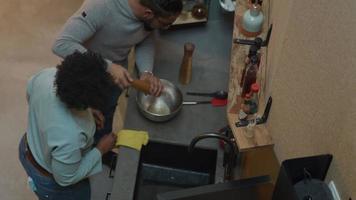svart mogen kvinna och svart man bär glasögon, står vid köksbänken bredvid henne, kvinnan tar bort borsten, mannen blir pepparkvarn, peppar i skålen, kvinnan skakar skål