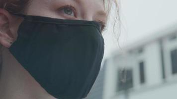 close-up de uma jovem mulher branca do lado de fora, usando máscara, olhos fixos video