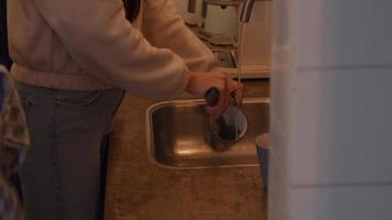 jovem mestiça lavando pratos, limpa copo com pincel, com água corrente, dá copo para jovem homem do Oriente Médio ao lado dela, que limpa copo com pano de prato