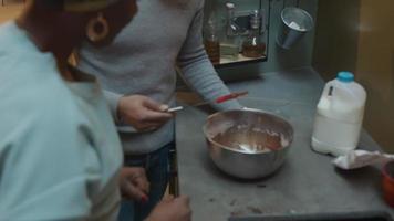 svart man lägger skrapan i skålen, tar lite tårtblandning med fingret, svart mogen kvinna, tar lite tårtblandning med fingret, båda smakar blandningen genom att sätta fingret i munnen