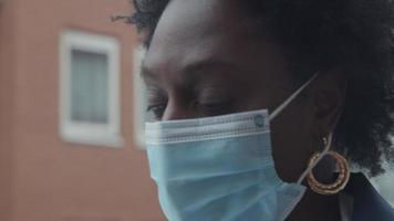 close-up de uma mulher negra madura do lado de fora, usando máscara, olhos e cabeça virados para a câmera