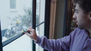 jovem homem do Oriente Médio limpa moldura de janela com esponja