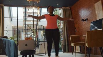 schwarze reife Frau, die im Wohnzimmer steht, springt und ihre Arme bewegt, Übungsklasse online mit Laptop neben ihr macht video
