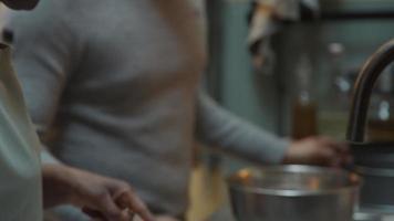 mulher negra madura lê receita, homem negro de óculos coloca a mistura para bolo na tigela, mulher abre a garrafa de leite, ambos conversando video
