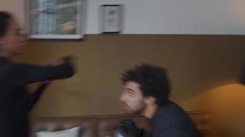 jovem mestiça com as mãos na frente, o braço se movendo acima da cabeça de um homem do Oriente Médio que se abaixa e dá um soco na mão com luvas de boxe