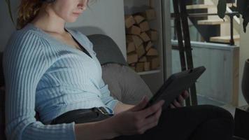 jovem branca sentada na sala de estar com fone de ouvido nas orelhas, mastigando, assistindo ao tablet no colo, luz da tela refletida nos olhos e no rosto