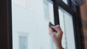 jovem homem do Oriente Médio limpa janela com esponja e fala