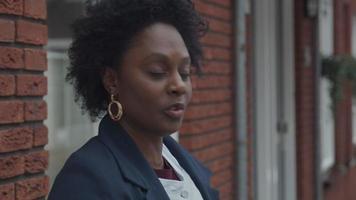 mulher negra madura fala com jovem branca do lado de fora, olhando-se à distância, mulher branca escuta