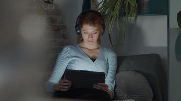 jovem mulher branca sentada na sala de estar, fone de ouvido nas orelhas, assistindo tablet no colo, luz da tela reflete nos olhos e no rosto, pega pipoca e coloca na boca