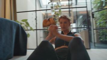 jovem mulher branca sentada na sala de estar no chão, joelhos dobrados, costas levantadas, mãos cruzadas, braços movendo-se para o lado, fazendo aulas de ginástica online
