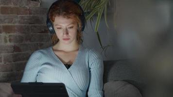 jovem mulher branca sentada no canto da sala de estar, fone de ouvido, comendo pipoca, assistindo tablet no colo, luz da tela refletindo nos olhos e no rosto