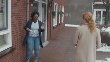 zwarte rijpe vrouw loopt naar buiten en ontmoet jonge blanke vrouw, van het tegenovergestelde, beiden zetten gezichtsmasker op, praten, lopen verder video