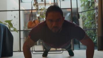 homem negro fazendo flexões no chão da sala de estar
