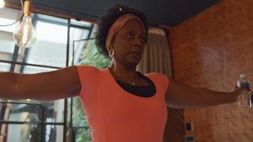 mulher negra madura em pé na sala de estar, segurando duas garrafas de água cheias à sua frente com os braços dobrados