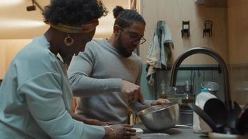 svart mogen kvinna och svart man bär glasögon, står vid köksbänken, mannen rör sig i skål med visp, kvinnan viker pappersform och sätter på ugnen, öppnar ugnen