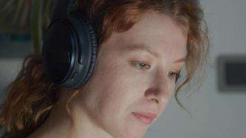 junge weiße Frau Kopfhörer auf Ohren, isst Popcorn, beobachtet Laptop, Bildschirmlicht reflektiert auf Augen und Gesicht