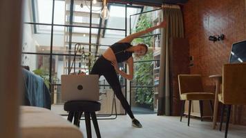 jovem mulher branca em pé na sala de estar, movendo os braços e as costas, as pernas escancaradas, fazendo aulas de ginástica on-line com o laptop na frente dela