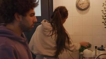 Joven mujer de raza mixta limpia los azulejos de la cocina en la pared con un paño, el joven del Medio Oriente en la parte delantera limpia la taza con un paño de cocina, habla, mira a la mujer, la mujer habla, limpia la tetera