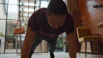 zwarte man met handen en tenen op de vloer, gestrekt lichaam, een been buigen, het in verschillende richtingen bewegen, gaat op de knieën zitten, lacht, ademt, kijkt omhoog en lacht
