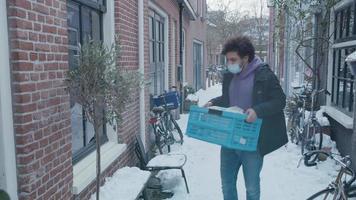 Jeune homme du Moyen-Orient avec un masque facial apporte une caisse avec des produits d'épicerie à une jeune femme métisse, ouvre la porte, une caisse à la porte, parle, dit au revoir, elle prend une caisse, l'homme part video