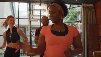 mulher negra madura em primeiro plano, jovem branca e homem negro no fundo da sala de estar, fazendo movimentos de dança simultaneamente, mulher negra conduz, todos se divertindo muito