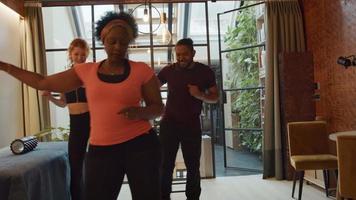 mulher negra madura em primeiro plano, jovem branca e homem negro no fundo da sala de estar, fazendo movimentos de dança simultaneamente, mulher negra conduz, se divertindo