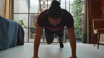 homem negro com as mãos e os dedos dos pés no chão, alongando o corpo, dobrando uma perna, movendo-a em várias direções, trocando de perna fazendo o mesmo exercício