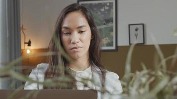 ung kvinna med blandat ras tittar på skärmen av bärbar dator i vardagsrummet