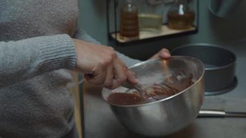 svart man bär glasögon och svart mogen kvinna, står vid köksbänken, mannen rör sig i skålen, häller kakmix i pappersform, kvinnan håller burken med båda händerna
