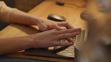 dedos de uma jovem branca digitando nas teclas do laptop