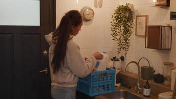 jovem mestiça na cozinha tira mantimentos da caixa, abrindo espaço para eles