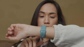 jovem mulher de raça mista segurando o braço com smartwatch na frente dela, tocando smartwatch