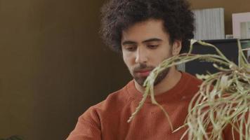 ung man från Mellanöstern sitter vid bordet och tittar på den bärbara datorn framför honom video
