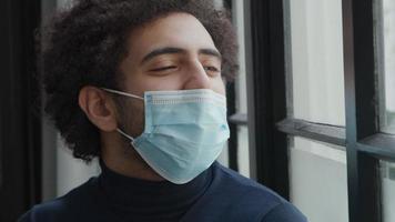 Gros plan du jeune homme du Moyen-Orient avec masque facial, regarde à travers la fenêtre, parle, masque descend, l'homme ajuste le masque sur le nez video