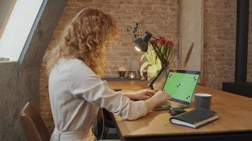 jovem branca se senta à mesa, assiste laptop com tela verde e começa a digitar