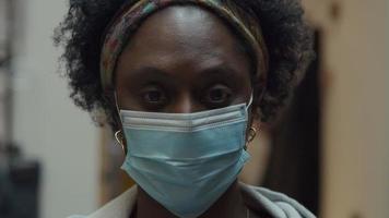 close-up de uma mulher negra madura com máscara facial, olhando pela lente da câmera, piscando video